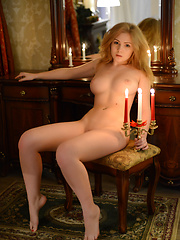 Marvelous busty long haired hottie posing absolutely naked in the romantic candlelight.