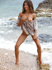 Divina A enjoys a nude stroll on the beach