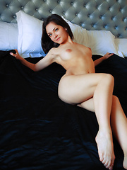 New model Lily White poses on the bed as she bares her delectable body.